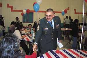 Photo by Philena Philip  Pinon Army Junior ROTC Instructor Sgt. 1st Class Miguel A. Rodriguez  shakes hands with parents of the cadets.