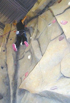 Photo by Rick Abasta In addition to a new game room, weight room, aerobics, yoga, massage therapy and basketball, community members also get to enjoy this indoor rock climbing wall.