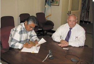 Photo by George Hardeen Navajo President Joe Shirley Jr. signs a historic document that removes the Bureau of Indian Affairs from the process of approving Navajo business site leases. Attending the signing is Interior Dept. Associate Deputy Secretary Jim Cason.