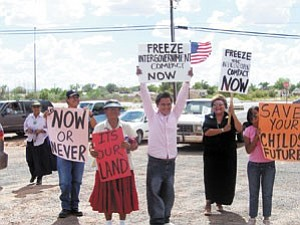 Photo by Joetta Goldtooth Prior to filing the injunction in opposition of the proposed Navajo-Hopi Land Settlement, approximately 40 residents marched through the streets of Tuba City arriving at the Tuba City District Court House where the injunction was filed and a rally held. Pictured above are Dine protestors Mae Tacheenee (left/center with red sign), Keith Jackson Jr. and Joetta Goldtooth who were joined along the march by numerous unknown supporters.