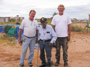 S.J. Wilson/Observer Robert Bowman, Merrill Sandoval and Craig Bowman look out at the foundation of the veteran's home which the Bowmans have volunteered to build for the elderly Code Talker.
