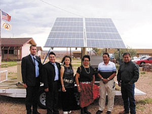 S.J. Wilson/Observer Michael Elliot, left, David Melton, Rayola Werito, Chapter Delegate Evelyn Acothley, Teddy Bedonie and Jack Colorado stand in front of the New Mexico model of Sacred Power Corp's solar settup. The Cameron model will include a wind turbine instead of a propane generator and a refrigerator.