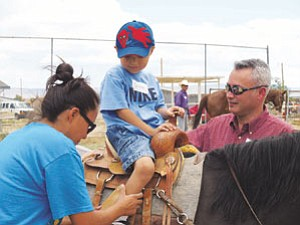 Photo by Carol Holyan  Glorinda Curley, Navajo Nation Department of Youth community involvement specialist, and David Rousch, a certified life coach from Tucson help young equestrian Triston Smith adjust his saddle for a comfortable ride.