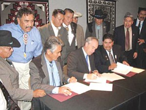 Navajo President Joe Shirley Jr., Interior Secretary Dirk Kempthorne and Hopi Vice Chairman Todd Honyaoma signed the historic Navajo-Hopi Intergovernmental Compact at the Heard Museum in Phoenix on Friday. Watching the signing, from left to right, are Council Delegates Harry Williams, Navajo Nation Council Speaker Lawrence T. Morgan, Duane Tsinigine, Shonto Harry Brown, Raymond Maxx, Leslie Dele former Hopi Tribal Chairman Wayne Taylor and former Navajo President Albert Hale (Photo courtesy of Navajo Nation Office of the President and Vice President).