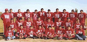 The KMS football team poses for a team shot earlier this season. The KMS varsity football team finished their season with an undefeated record of 6-0. Games played were against Red Mesa, Ganado, Tuba Public, Tuba Boarding, and Shonto Prep. KMS capped off their season with a tough game win against Page Middle School for the conference champion's title (this is the 2nd undefeated KMS football team in the last 4 years). Parents of the players are to be commended and thanked for their hard work and constant support. Players pictured from left to right are: (back row) Coach Fred Todachine, Jeffery Staley, Delvin Holiday, Ryan Bekaye, Quintin Manygoats, Shawn Speck, Stenson Osif, Ethan Sherlock, William Tsosie, Kamerson Isaac and Kyle Hall, (middle) Manager Robin Sands, Dakota Kaye, Alan Todachine, Paige Begay, Irwin Kaye, Orin Whaley, Pierson Bronston and Manager Deidre Wilson, (front) Junior Manager ShonRae Whitehair, Bowdrie Black,Tedrick Joe, Joshua Holiday, Bradford Seaton, Mathew Blackhorse, Nelentino Hardy and Manager Alannah Yazzie.