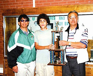 "TC Jr. High head cross-country coach Arvis Myron (left) stands with eighth-grader and 2006 Jr. High cross-country Individual Champion Bill ""Billy"" Orman (center), son of Teresa and Dr. William Orman. Holding the state trophy is TCJHS Principal Lee Tsingine (right).  Orman is a first time competitor making his state title all the more astounding (Photo by Byron Poocha/TCUSD)."