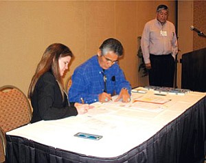 Navajo Nation President Joe Shirley Jr. signs an agreement between the Navajo Nation and the state of Arizona Dec. 14. Pictured with President Shirley is Tracy Wareing, the director of the Arizona Department of Economic Security. The agreement will benefit Navajo foster children. The children will now be allowed to be raised and nurtured by their own relatives (Photo by George Hardeen).
