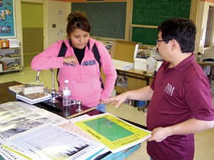 McKinley County Extension 4-H agent Richard Ng discusses the levels of radiation found at the Church Rock uranium spill site with Fort Wingate student Renee Cleveland. Cleveland, who participated in gathering the data while mapping the area, plans to use the information as a science project (Photo by Jane Moorman).