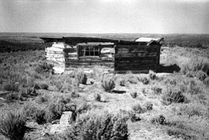 The devastation—an abandoned hogan on Big Mountain with the Black Mesa Coal mine in the distance (Photo and text by Serle L. Chapman, originally published in  his 2001 work, We the People,  Of Earth and Elders, Volume II).