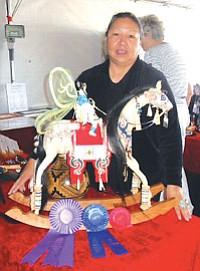 "Best in Show winner Imogene Goodshot Arquero from Santa Fe, N.M. with her sculpture figure called ""Native Mystics."""