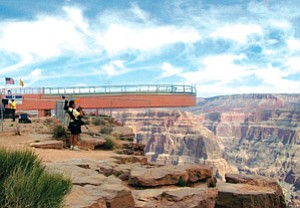 An unidentified photographer cautiously takes in the breathtaking view of the Grand Canyon from the West Rim as the newly christened skywalk hangs over the majestic backdrop. The Hualapai Tribe hopes that the skywalk will bring in much-needed tourism revenue (Photo by Jackie Brown).