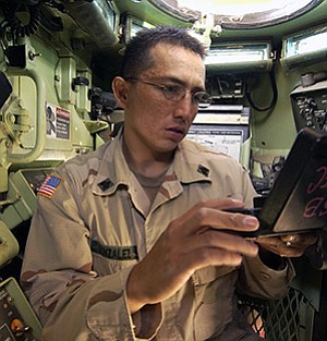 "Army Sgt. Christopher ""Gonzo"" Gonzalez programs radio frequencies into the communications systems in an M1A1 Abrams Main Battle Tank prior to a mission in Baqubah, Iraq, on May 27, 2005. Gonzalez, part of the 3rd Brigade Troop Battalion, 3rd Infantry Division, was the eighth Diné soldier killed in Iraq or Afghanastan (Photo by Staff Sgt. Suzanne Day/U.S. Department of Defense)."
