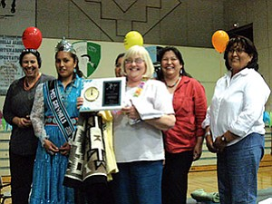 Alice Dunford (center) with the Greyhills school board administration and Miss Greyhills Mashayla Smith receiving a gift of a Navajo rug.