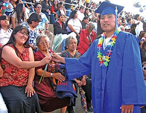 Hopi High graduate Alan Gonnie presents a rose to his proud mother (Photo by Stan Bindell/Observer).