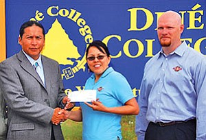 Diné College President Ferlin Clark (left) receives a check for $20,000 from Roxie June and Executive Vice President John Snider of Nova Corporation. The check will establish the Nova Corporation Scholarship Fund to benefit Diné College students attending campus sites throughout the Navajo Nation (Photo by Ed McCombs).