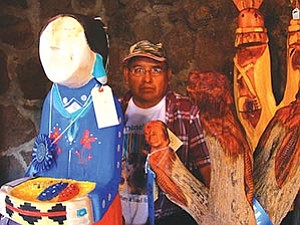 "Harry Benally of Sheep Springs, N.M., with two of his ""Diné Lady"" sculptures. Benally took first place in the Folk Art category with the carving on the left. The carving on the right brought Benally an honorable mention in the sculpture division (Photo by S.J. Wilson/Observer)."