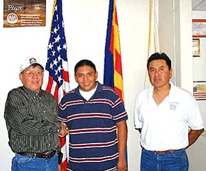 Tonalea Chapter president Chester Claw (left) and secretary Franklin Tohannie (right) congratulate Jordon Begay (center) for receiving various scholarships including the Gates Millennium Scholarship.