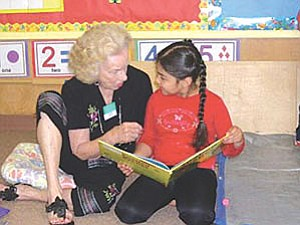 A volunteer reads to a five-year-old at the Pathways to Learning Kindercamp—one of many successful programs instituted in northern Arizona by Alliance for Children's Early Success (ACES). This literacy camp takes place in Flagstaff Unified School District elementary schools for five weeks during the summer (Courtesy photo).