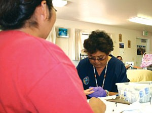 Rosey Jones, Health Education technician from Montezuma Creek, Utah performs a health screening for Gloria Sam during Health Fair activities at the San Juan Senior Center held in Bluff, Utah, Aug. 29.