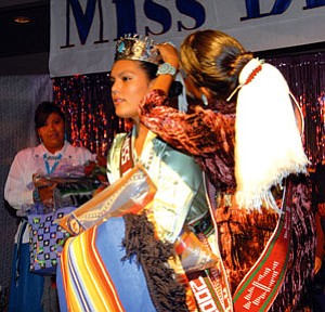 Blaire Belle Maryboy (right) places her crown on Danielle Coralynn Goldtooth Sept. 19 as she was crowned Miss Diné College 2007-2008 (Photo by Edward McCombs).