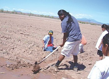 North Leupp Family Farms also serves as an educational opportunity for area students. Here, Justin Willie helps children prepare to plant earlier this year (Photo by S.J. Wilson/NHO).