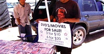 A still shot from a documentary by Andee and Shonie De La Rosa shows an unidentified Navajo man advertising the sale of illegally pirated copies of DVDs at a local flea market on the Navajo Reservation. The Navajo Nation is close to passing legislation which would make it illegal to copy and sell copyrighted CDs and DVDs of any kind on the Navajo Nation. If passed, this legislation will most likely be the first of its kind in Indian Country.