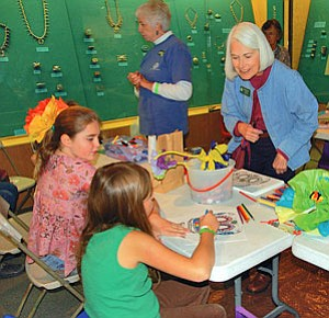 Jessi Thomas (left) and a friend make crafts with Museum of Northern Arizona Docents Phyllis Wolfskill (standing at center) and Nancy Easter (right) at this year's Celebraciones de la Gente.