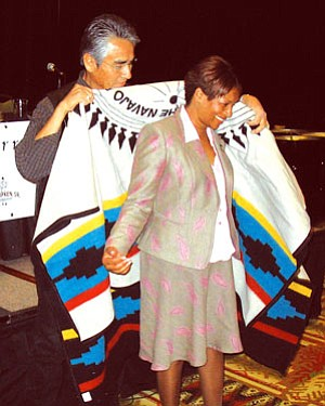 Navajo President Joe Shirley, Jr., presents former Assistant U.S. Attorney General Regina B. Schofield with a Pendleton robe with the Navajo Nation seal for her work on behalf of native children and tribes as director of the U.S. Justice Department's Office of Justice Programs. President Shirley joined other tribal leaders at the Hyatt Regency Tamaya at Santa Ana Pueblo (Photo by George Hardeen, NN-OPVP).
