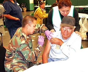 An unidentified elder from the Tuba City/Moenkopi area receives a flu shot during the community-wide mass vaccination drill held at the Tuba City High School Warrior Pavilion Nov. 29. In all, 278 people received their flu shots (Photo by Byron Poocha/TCUSD).