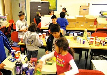 Students work hard preparing food baskets to be distributed to needy families (Courtesy photo).
