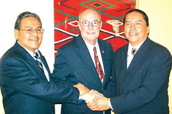 NMSU President Michael Martin (center) joins Elmer Guy (left), president of Navajo Technical College and Ferlin Clark, president of Diné College in a ceremonial handshake after they signed the Tribal Extension memorandum of agreement to formalize the schools working together to provide Cooperative Extension Service to the Navajo Nation people (Photo by Jane Moorman, NMSU).