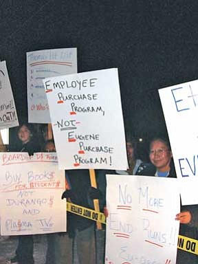 Protesters hold their messages high following the Jan. 9 Tuba City Governing Board meeting.