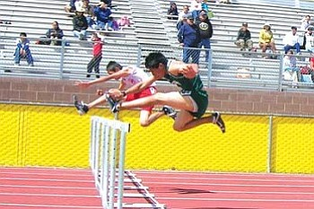 Darnell Phillips (foreground) of Tuba City battles a rival from Monument Valley in the 110-meter hurdles at the Chinle Wildcat Invitational.