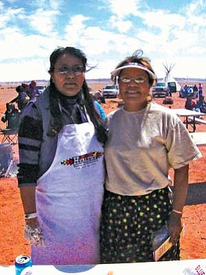 Judy Begay (left) and Jamescita Peshlakai were two of several women who prepared food for the Mother Earth gathering. The Peshlakai family provided an earth-oven roasted beef lunch complete with baked potatoes, vegetables, watermelon and frybread (Photo by S.J. Wilson/NHO).