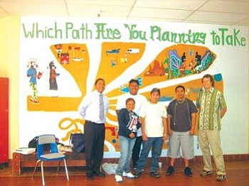 Students stand in front of a mural at Hopi High School that shows the careers and cultural ways that students might want to go and the choices they will have to make (Courtesy photo).