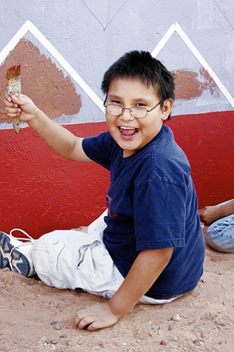 <i>Courtesy photo</i><br> An student with the Tuba City Boys and Girls Club of the Diné Nation smiles as he proudly holds up his paintbrush as he helped to complete a mural painted on the side of the Tuba City Community Center. The mural was part of an art-based youth exchange project.