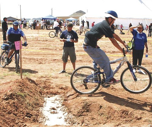 Tony Begay, 16, of Dilkon makes a jump over the advanced course mud puddle during the second annual Bike Rodeo on July 17 where bicycle safety was emphasized by the Navajo Nation Special Diabetes Project (NNSDP).