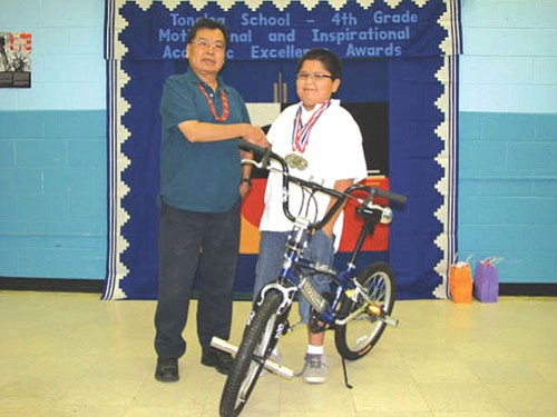 Mykelti Curley stands with Mr. Blake next to his new awarded bike received for perfect attendance all school year.