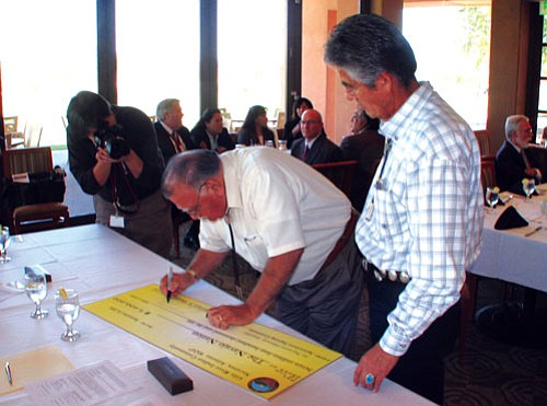 <i>Courtesy photo</i><br> Navajo Nation President Joe Shirley Jr. watches Gila River Indian Community Governor William Rhodes sign a $7.4 million check as part of a historic pooling agreement between the Navajo Nation, the Gila River Indian Community, the Fort McDowell Yavapai Nation, and the Tohono O'odham Nation. The agreement is expected to bring more than $130 million to the Navajo Nation over the next 17 years.