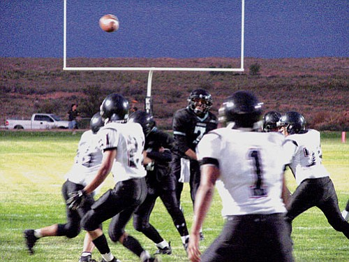 Quarterback Eliot Chee No. 7 passes over the top for a touchdown Friday night against the Many Farms Lobos.