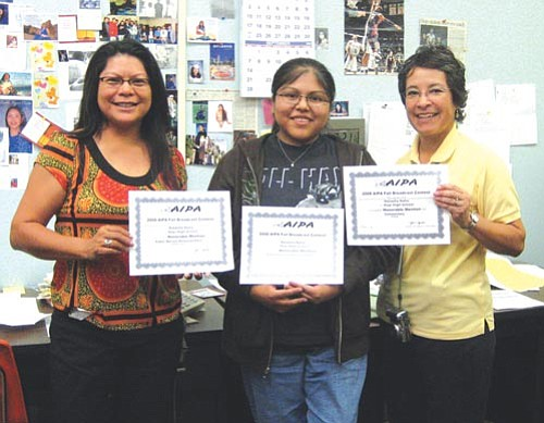 Patti Talahongva (Left) and Anita Luera (right) sandwich Natasha Naha and celebrate her winning three awards at state.