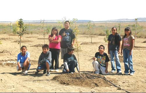 Young students pause while working on the orchard at First Mesa Elementary.