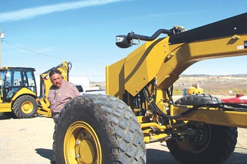 <i>Photo by Joshua Lavar Butler/NNOS</i> <br> Navajo Nation Speaker and Council Delegate Lawrence T. Morgan (Iyanbito/Pinedale) inspects a new Caterpillar road grader purchased for the Pinedale Chapter with Navajo Nation and State of New Mexico capital outlay funds. A backhoe was also purchased by the chapter and will be used for road repairs and maintenance, new homesite area leveling and other improvement projects for the chapter.