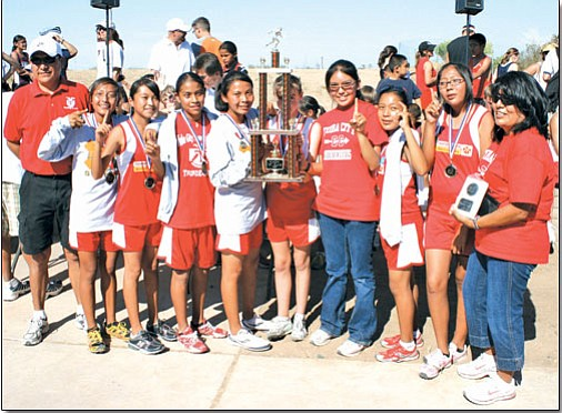 The state champion Tuba City Boarding School Lady T-birds (from left to right) Coach Phil Coolie, Mikayla Hudgins, Ashley Onsae, Amber Toledo, Jaylin Sanders, Brianna Loughran (standing behind the championship trophy), Dorshanna Coolie, Kairee Silas, Audrianna Honanie, and Coach Jewel Coolie.