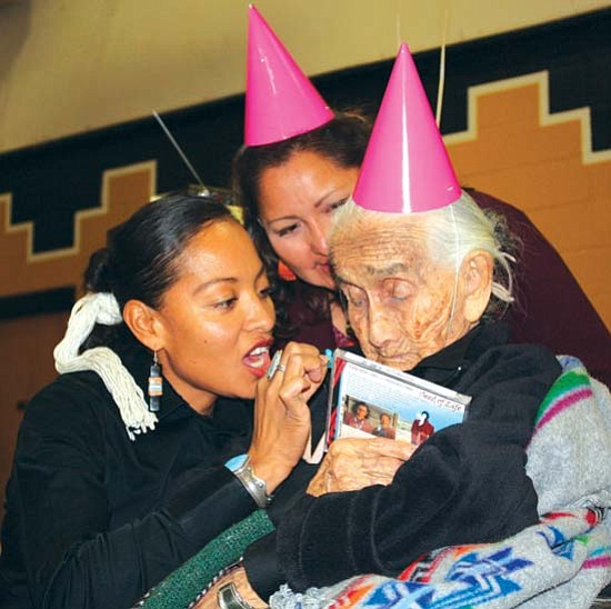 <i>Photo by Natasha Kaye Johnson</i><br> Radmilla Cody, award-winning recording artist, presents a turquoise horned toad to Nellie Rose and a music CD at her 108th birthday in Black Mesa.