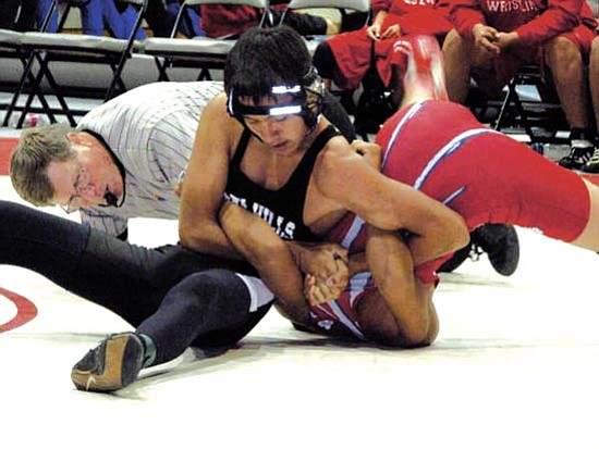 <i>Courtesy photo</i><br> Senior Garrett Manygoats of Greyhills Academy attempts a pin against Red Mesa's Donavan Eldridge as a referee checks the hold during wrestling multiples at Greyhills Academy High School on Dec. 10