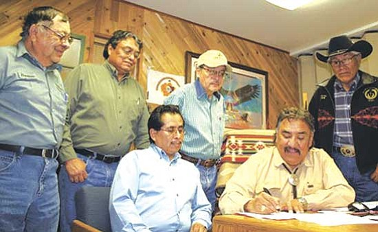<i>Photo by Natasha Kaye Johnson</i><br> Navajo Council Speaker Lawrence T. Morgan signed a memo of understanding with Navajo Transit System that resulted in the purchase of new buses and a $1.00 per day flat rate for public transportation. Pictured left to right, Harrison Watchman and Lee Bigwater with Navajo Transit System; Virgil Brown with Navajo Division of General Services; Council Delegate Young Jeff Tom; Speaker Lawrence T. Morgan; and Council Delegate Leslie Dele.