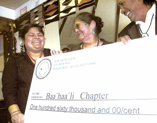 <i>Courtesy photo</i><br> Chapter staffer Guarena M. Adeky Skeets (far left) Anne Descheny (center), and Benjamin Livingston, react after Baahaali Chapter is presented with a check for $160,000 for LGA certification.