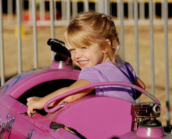 Trib Photo/Stew Schrauger<br>  Brinlee Kidd of Prescott Valley turns around to look back at her mother, while enjoying a kiddie ride at the 94th Yavapai County Fair, which ended Sunday.