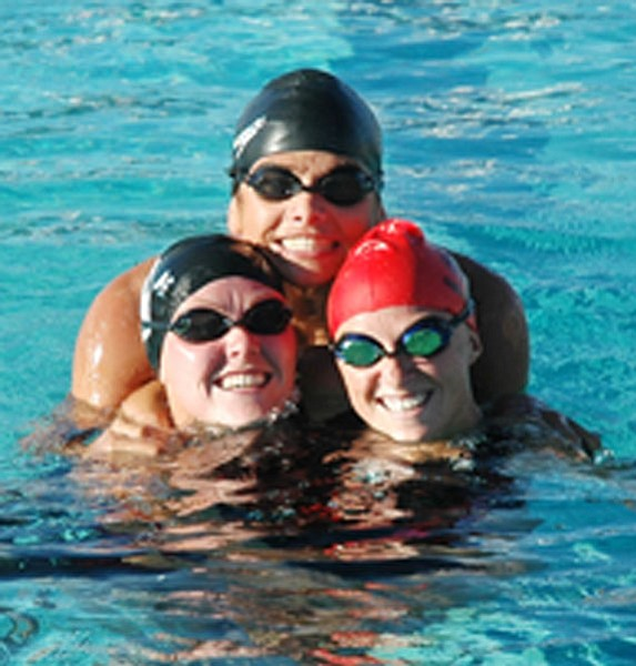 "Trib Photo/Cheryl Hartz<br> From left, Erika Heinbaugh, Chris Dodson and Christina ""C.J."" Jenkins mug for the camera before warm-up laps for a distance race at Bradshaw's final home swim meet of the season, Oct. 2."